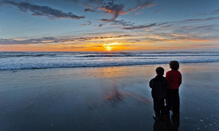 Dos niños mirando al horizonte con una puesta de sol costera. Foto de Quentin Surco.